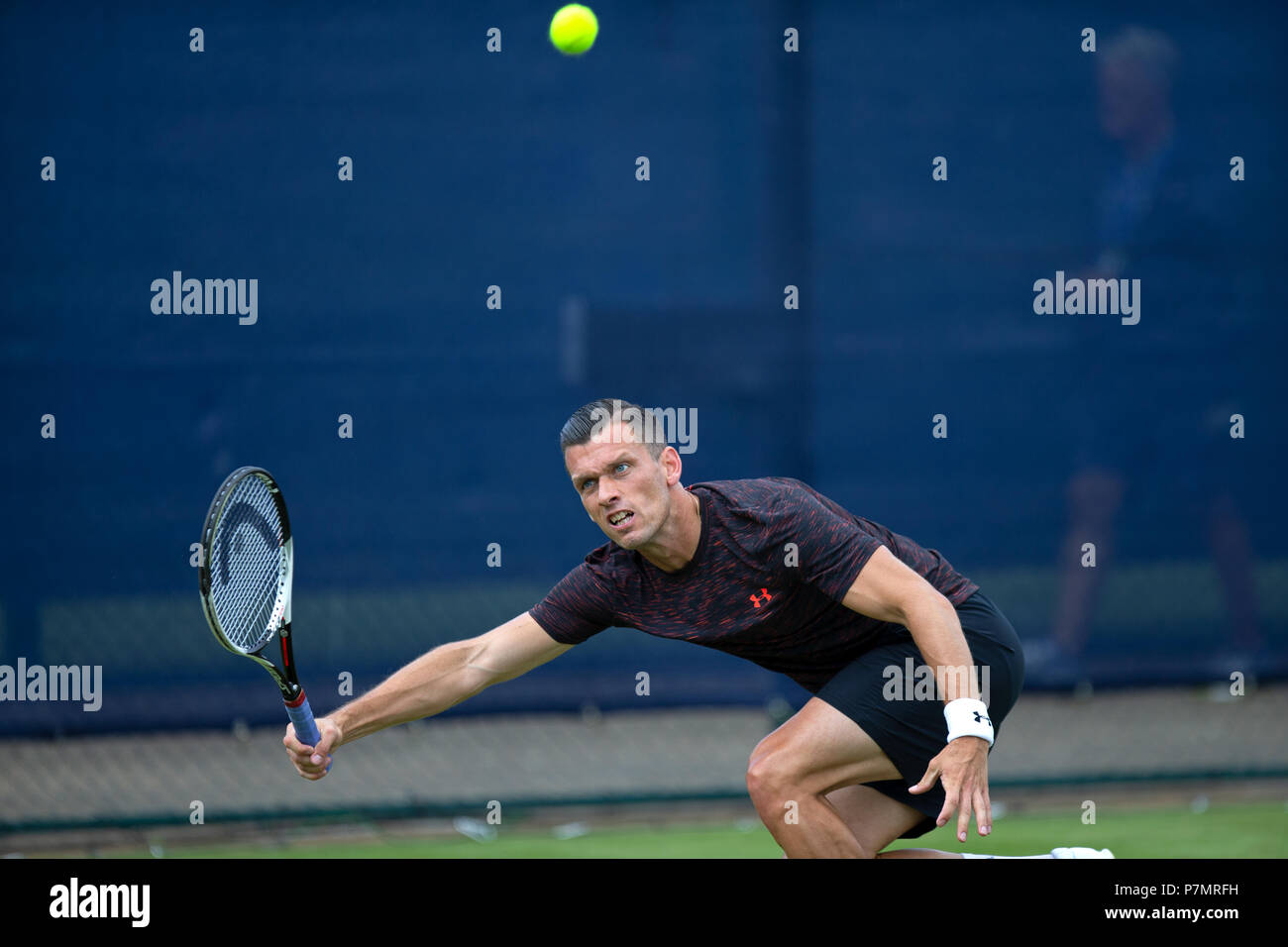 Tobias Kamke, professional tennis player, stretches for and plays a shot from the baseline during a match. - Stock Image