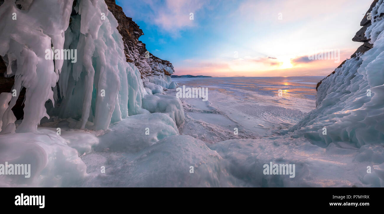 A panoramic picture the the ice stalactites in a cave at the shore at sunset at lake Baikal, Irkutsk region, Siberia, Russia - Stock Image