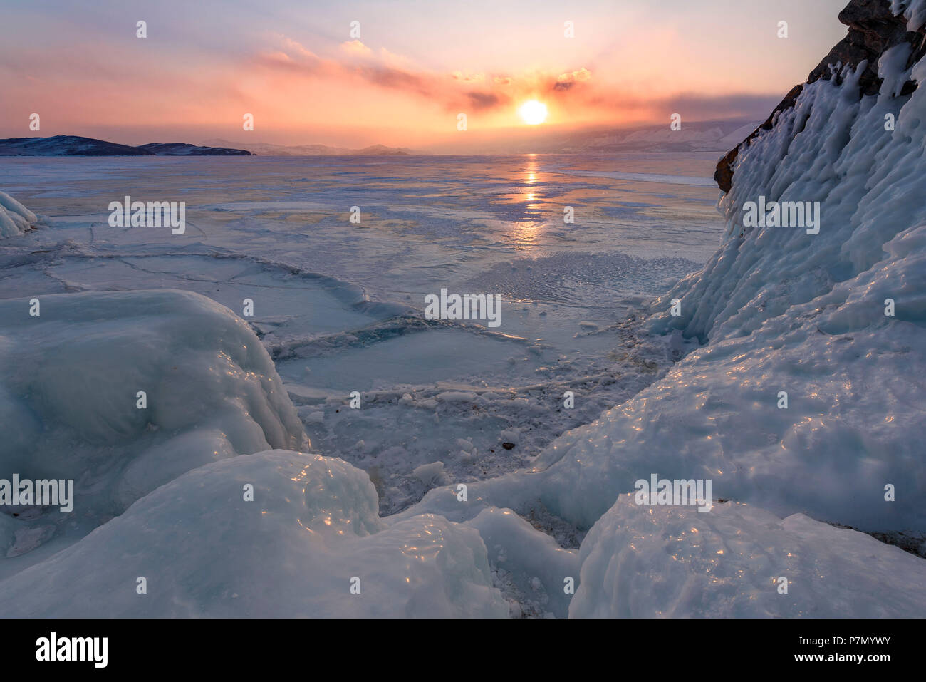 Ice stalactites in a cave at the shore at sunset at lake Baikal, Irkutsk region, Siberia, Russia - Stock Image
