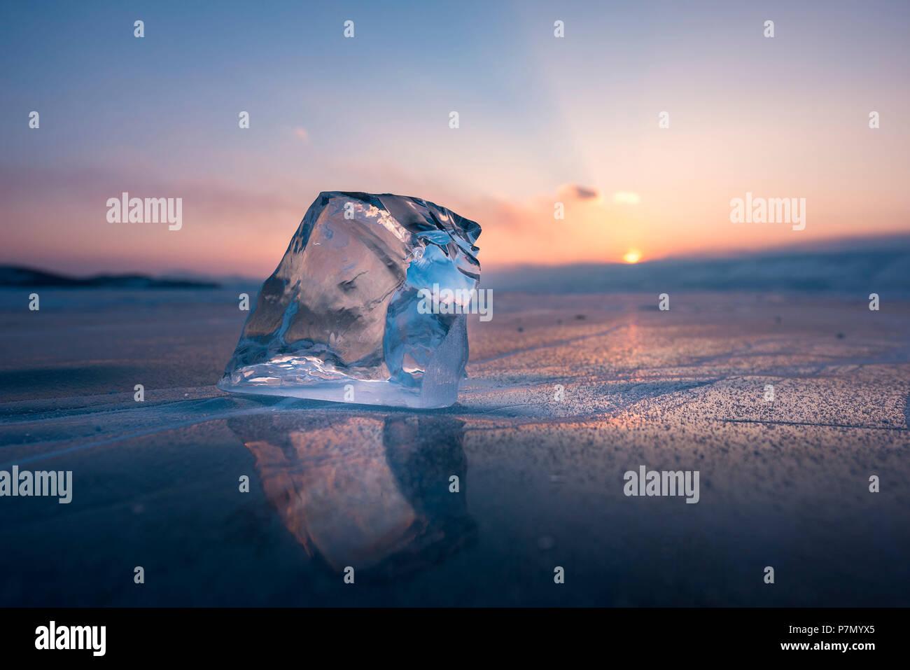 A cube of ice on the flat frosen lake at sunset, Baikal, Irkutsk region, Siberia, Russia - Stock Image