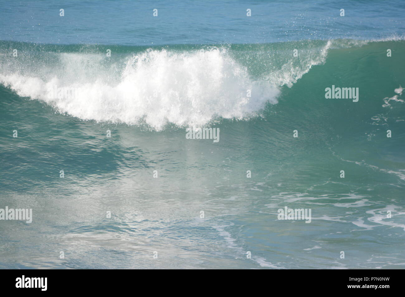 Crashing waves reflecting in water - Stock Image