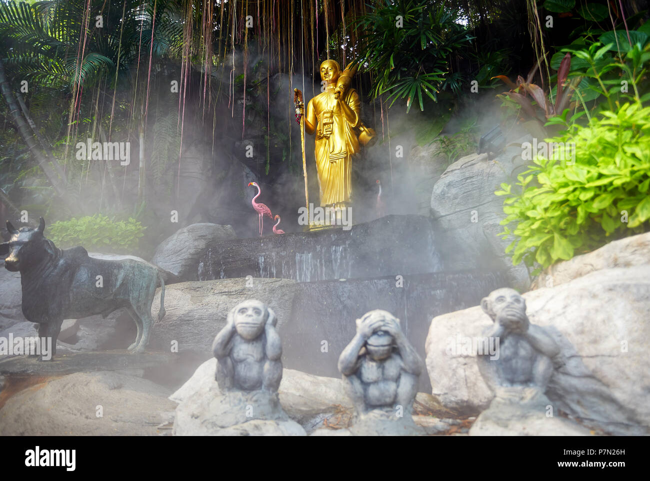 Golden Buddha statue in the tropical garden with waterfall in Wat Saket Golden Mountain Temple in Bangkok Stock Photo