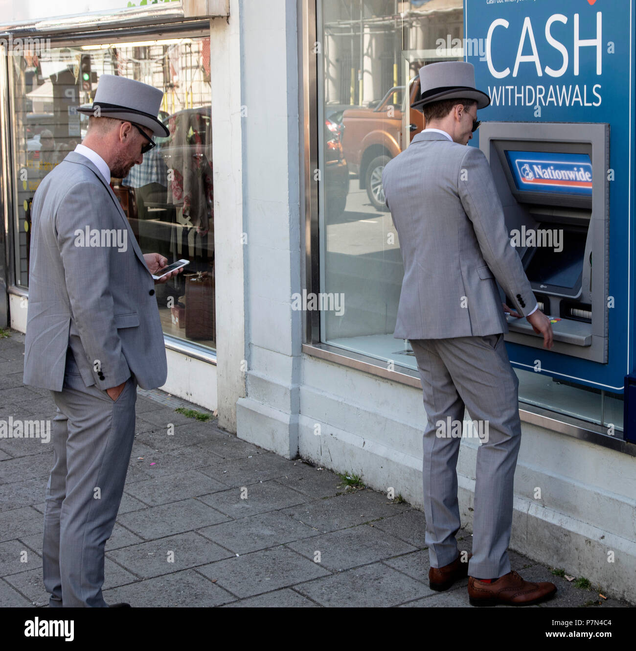 Two men at cash machine, ATM, dressed in top hats and grey suits for a wedding - Stock Image