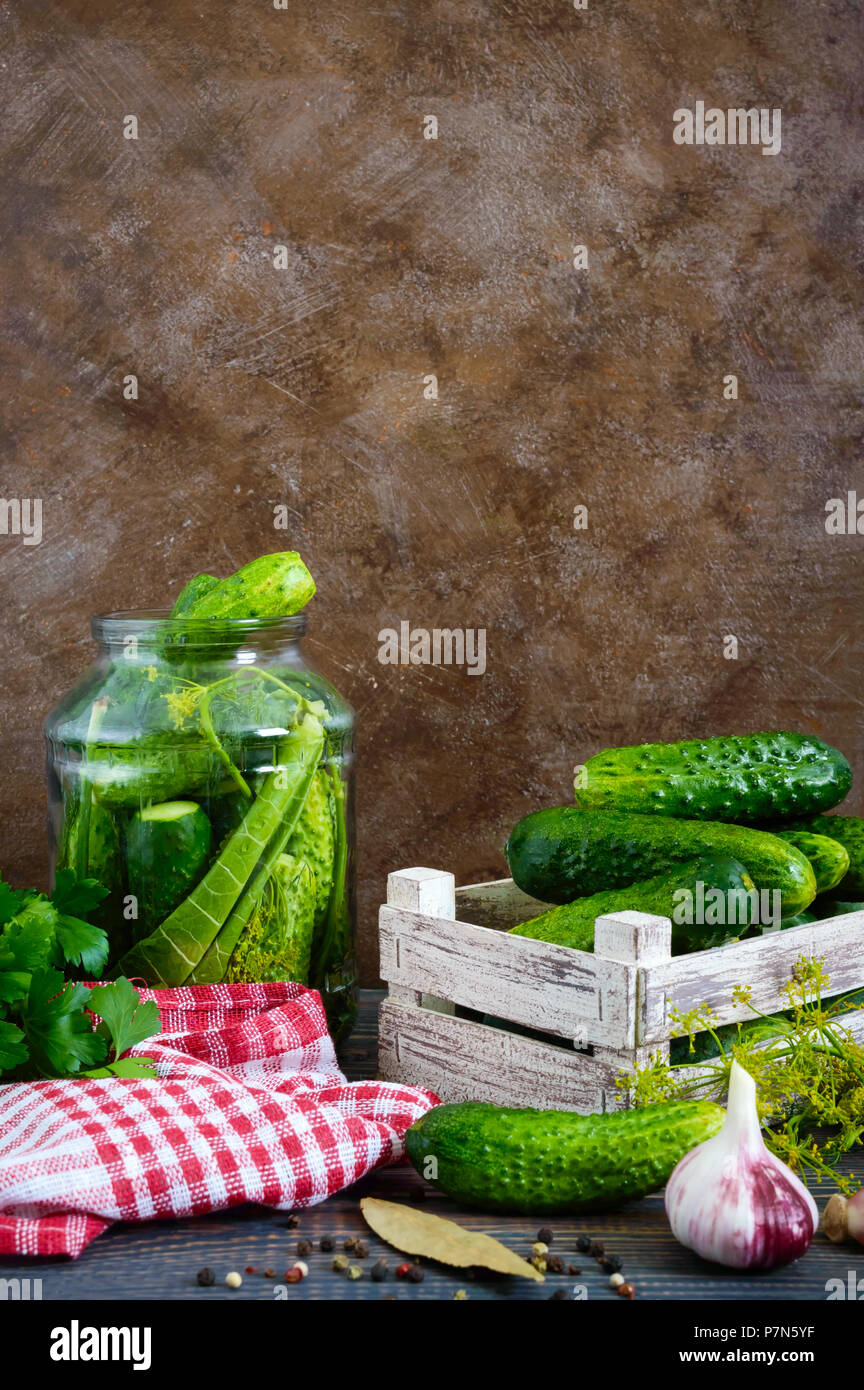 Pickles. Delicious pickled cucumbers in a jar, fresh harvest in a wooden box, spices, herbs on a table. Preparation of cucumbers for pickles. Vertical - Stock Image