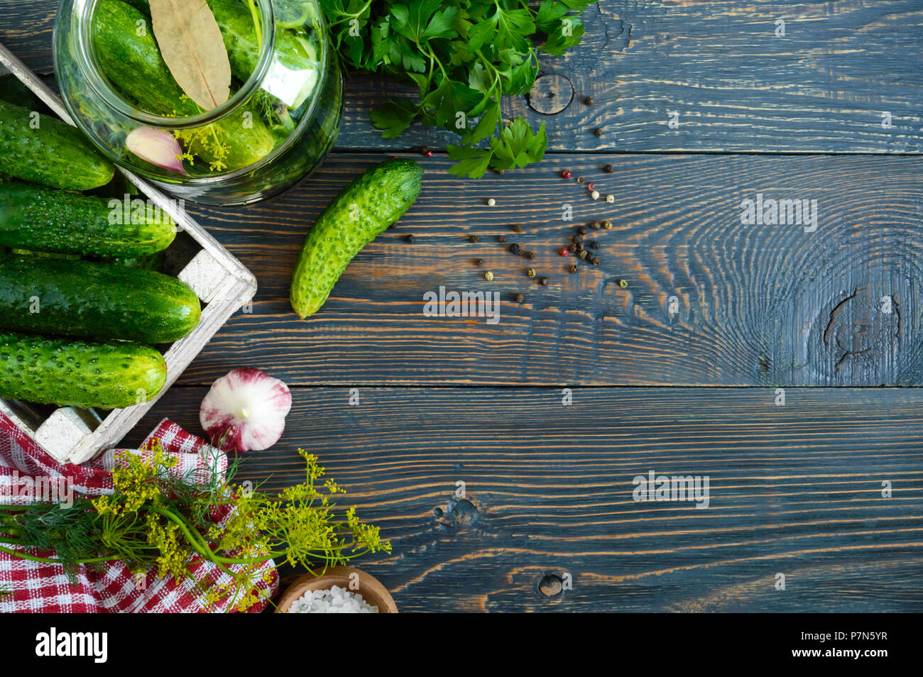 Pickles. Delicious pickled cucumbers in a jar, fresh harvest in a wooden box, spices, herbs on a table. Preparation of cucumbers for pickles. Top view - Stock Image