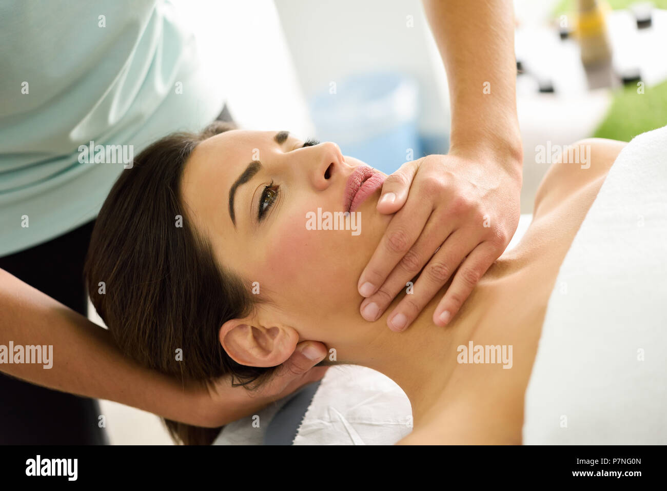 Young caucasian woman receiving a head massage in a spa center. Female patient is receiving treatment by professional therapist. - Stock Image