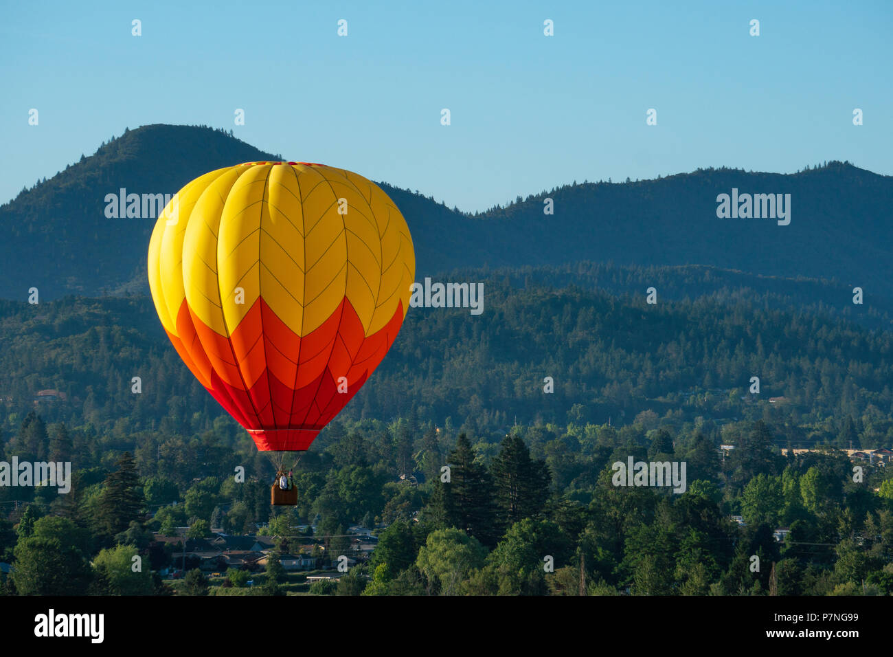 Hot Air Balloons Soaring Over Fields And Mountains During The Balloon Kite Festival In Grants Pass Oregon