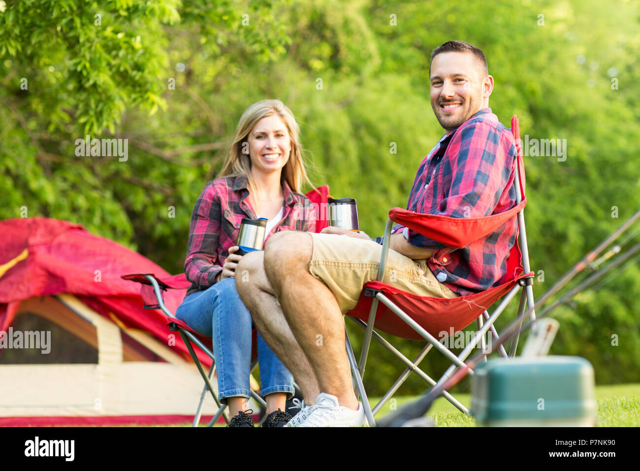 Couple talking and laughing on a camping trip. - Stock Image