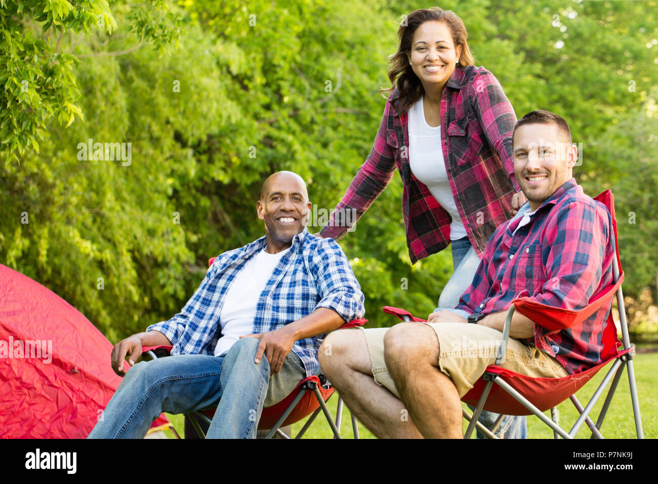 Group of friends laughing and talking. - Stock Image