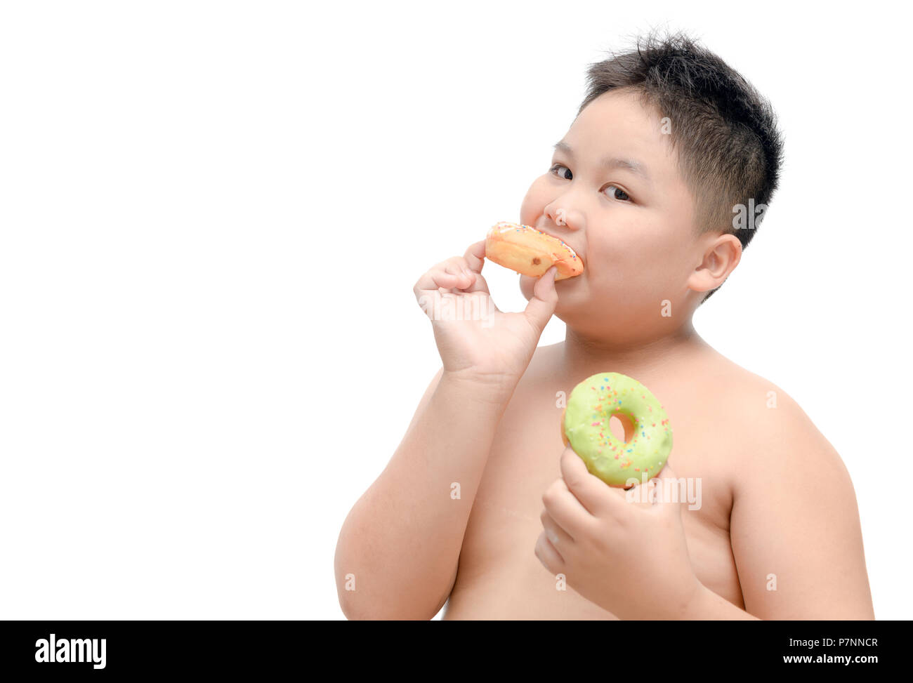 Obese fat boy is eating donut isolated on white background, junk food and dieting concept - Stock Image