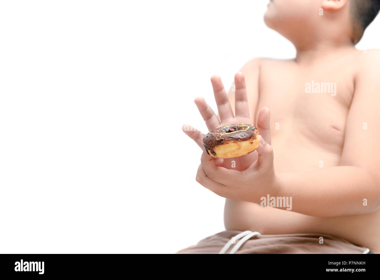 Obese fat boy refuses to eat donut isolated on white background - dieting concept - Stock Image