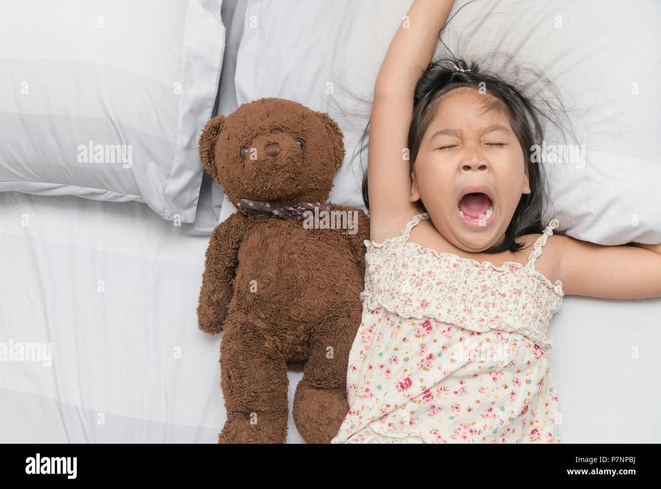 Little girl yawn and sleep on bed with teddy bear doll, Health care and relaxation concept - Stock Image
