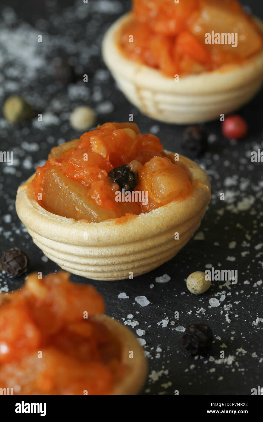 Mini canapes from a vegetarian ragout (stew)  on a black background - Stock Image