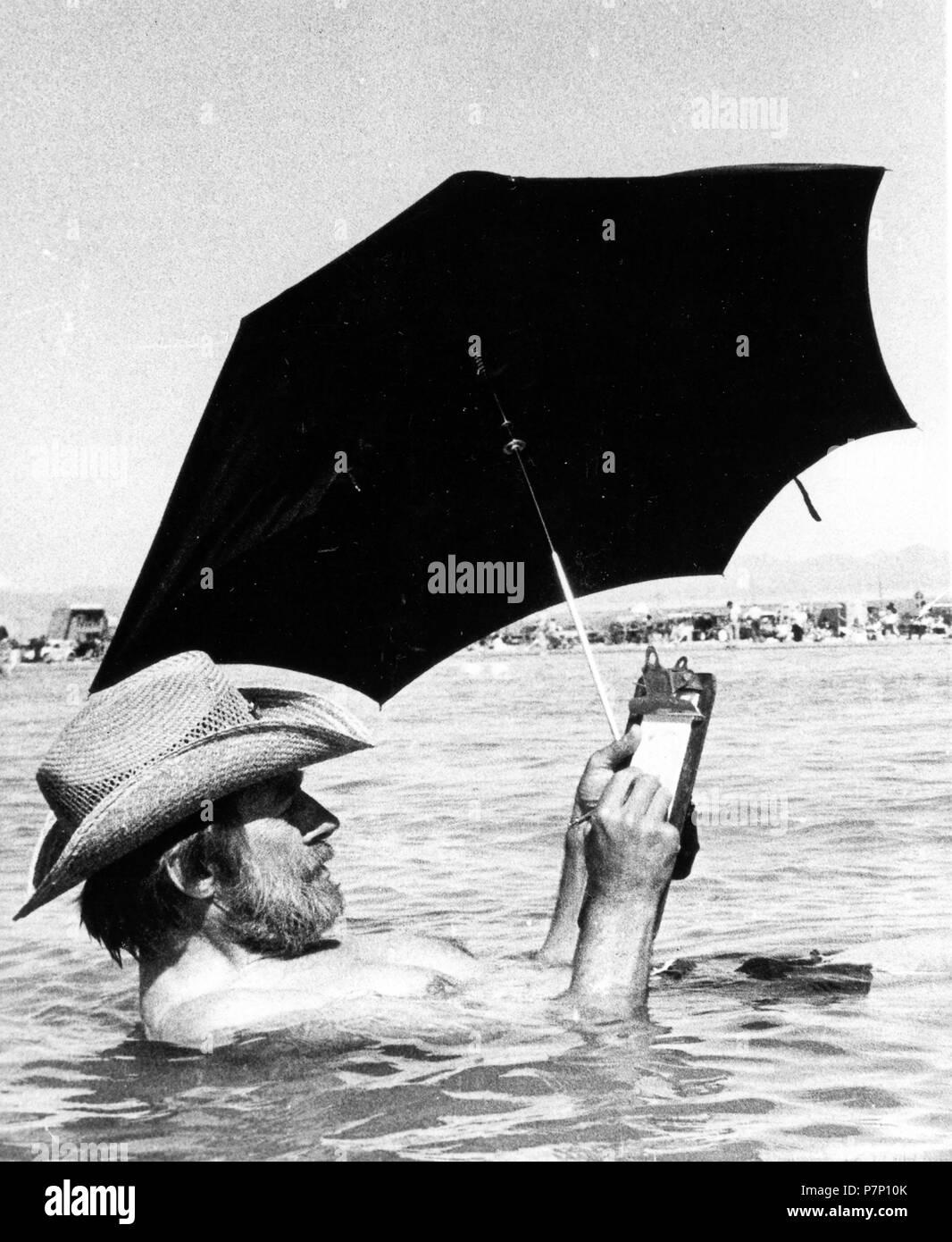 Man with parasol in water, Mexico City, Mexico - Stock Image