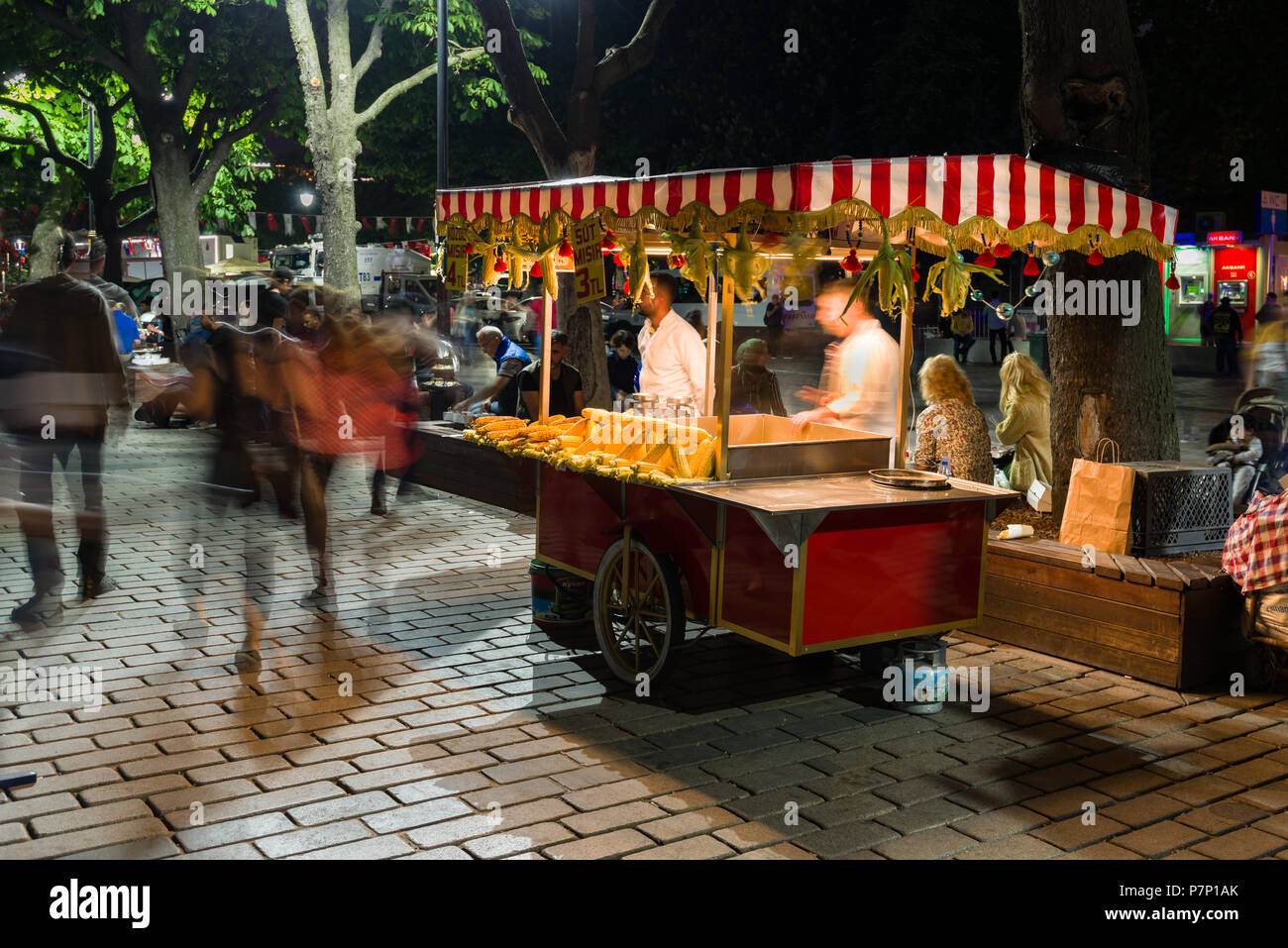 A small food stall selling corn on the cob or milk corn (Süt Mısır) with people walking past at night, Istanbul, Turkey - Stock Image