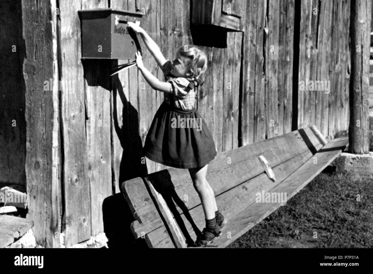 Girl trying to reach mailbox, ca. 1930, exact place unknown, Germany - Stock Image