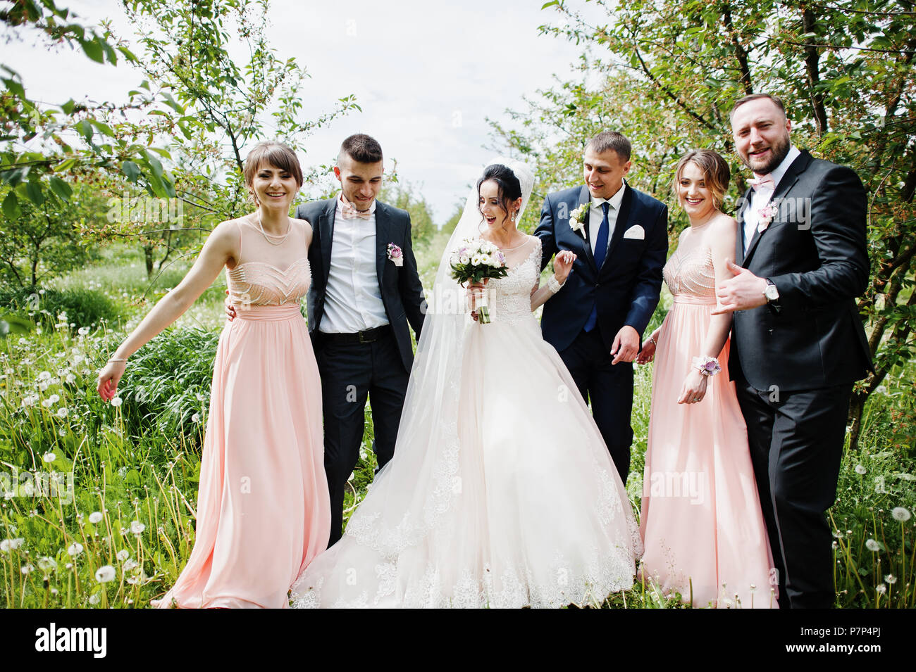 Groomsmen With Bridesmaids And Wedding Couple Posing In The Garden Outdoors Stock Photo Alamy