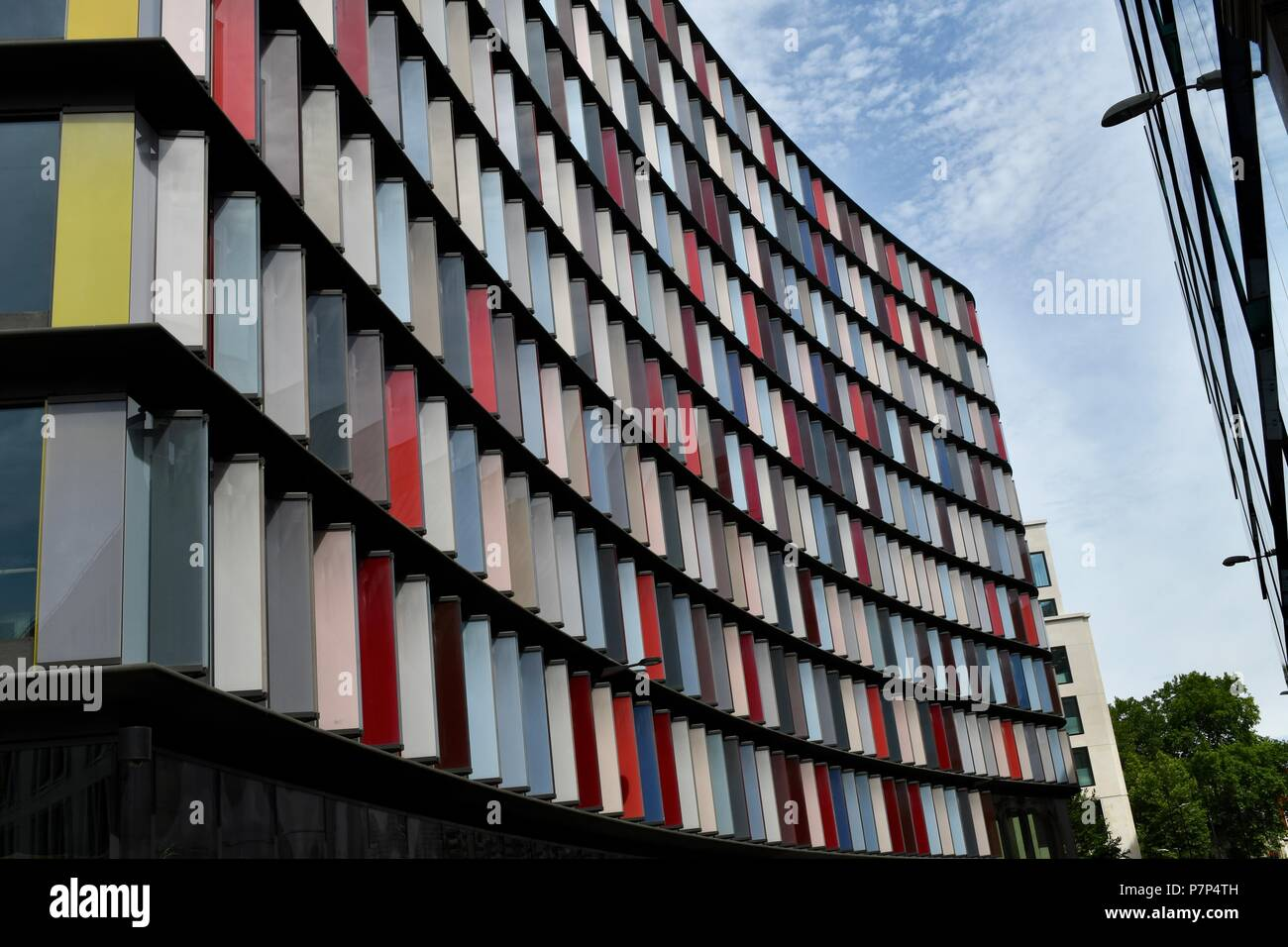 Modern building with colourful glass panels as protection against the sun - Stock Image