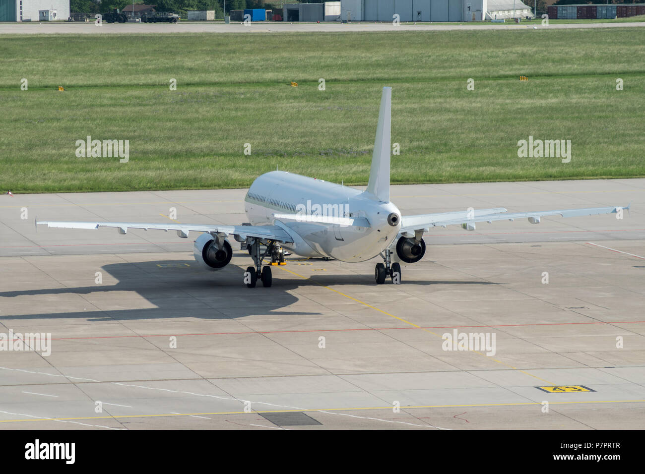 white airbus is waiting at stuttgart airport on parking position, germany - Stock Image
