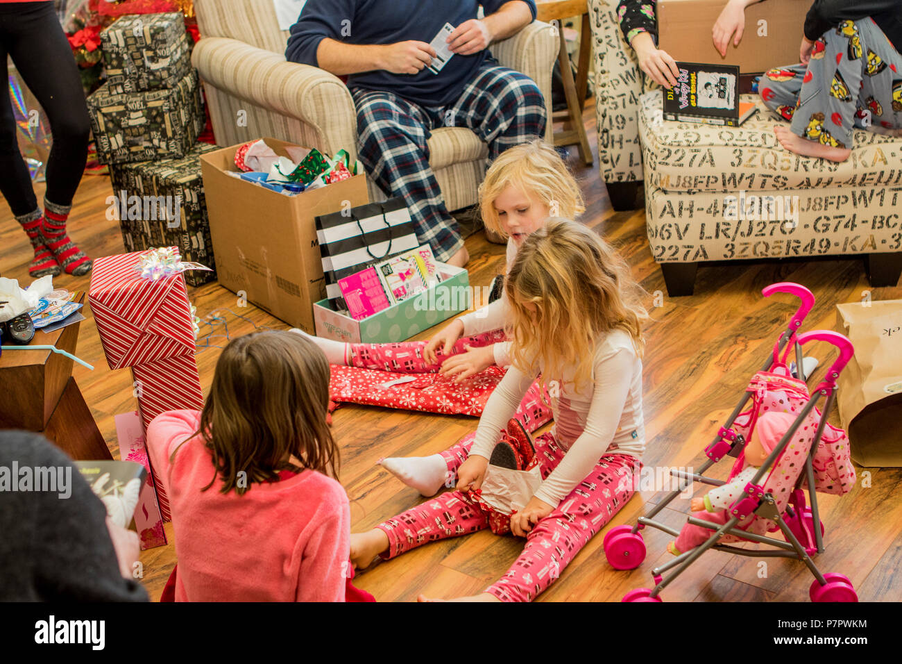 Three young girls, aged 3 to 8, sitting on floor as two open presents. Cranbrook, BC, Canada. Modlel released- front blonde #114 rear blonde #113 dark - Stock Image