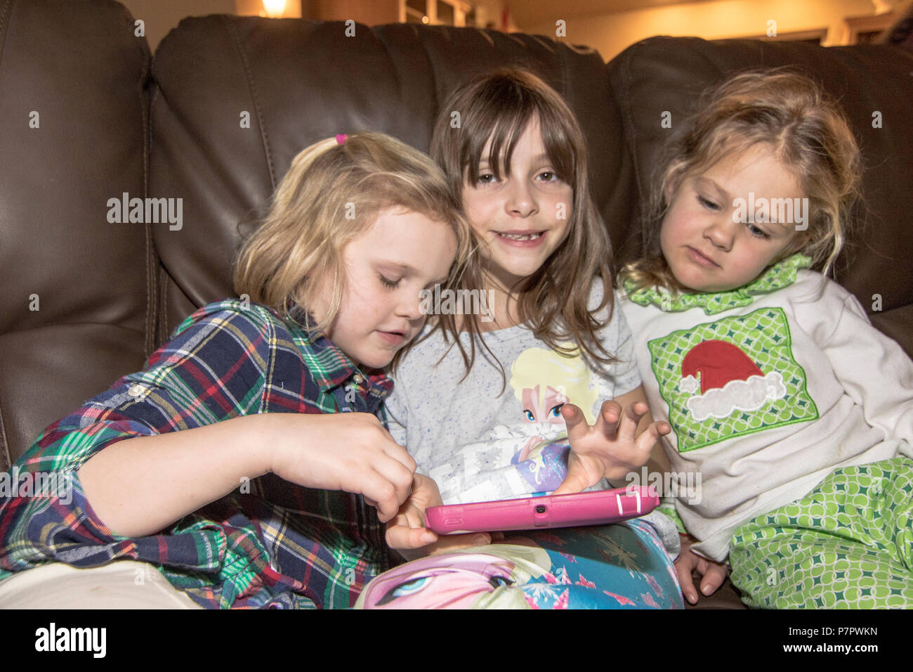 Three pretty, girl cousins,  playing with tablet, cuddled  on chair. Cranbrook, BC, Canada. Modlel released- left to right-#113, #104, #114 - Stock Image