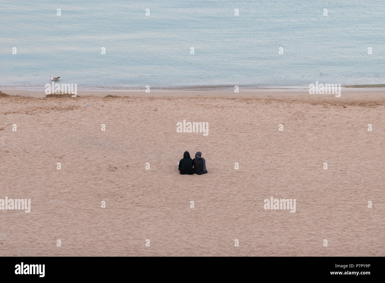 Two women with hijabs sitting on their backs in the sand of Quemado beach at sunset in Al Hoceima, Morocco - Stock Image