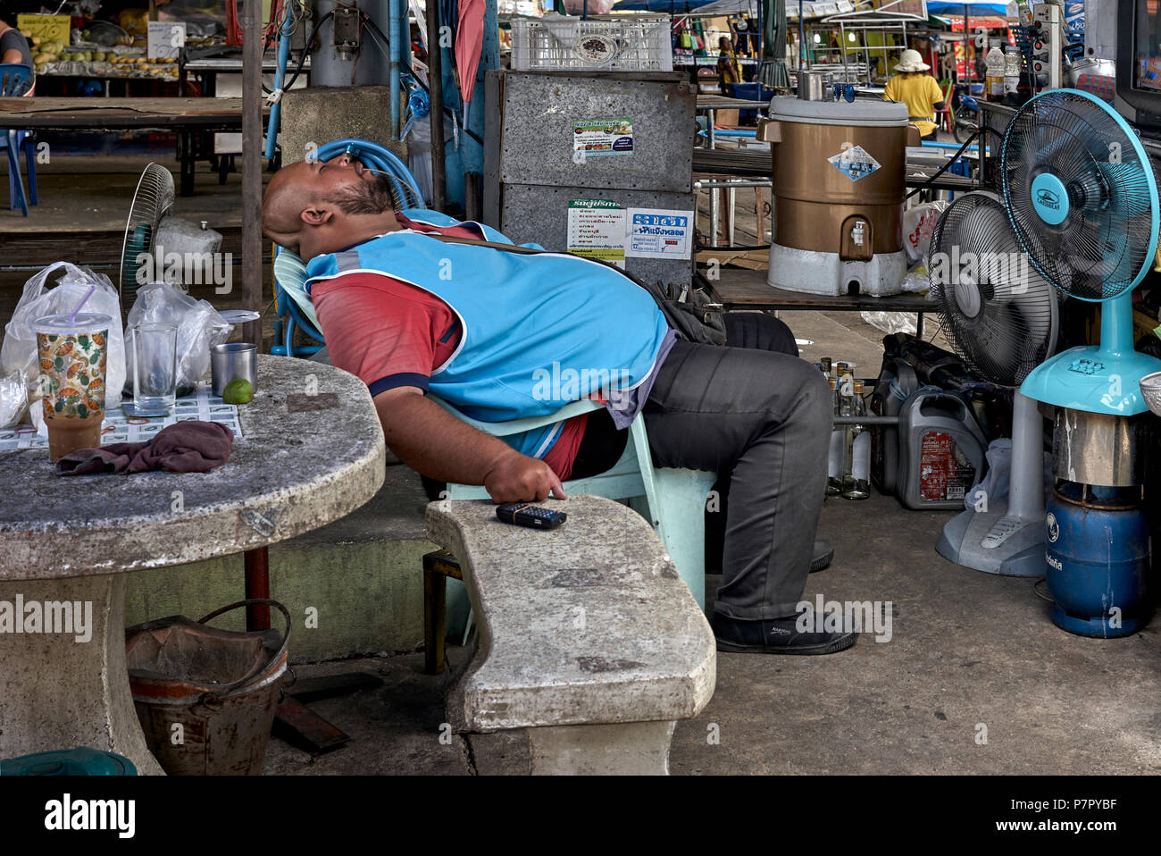 Thailand. A very hot day and a large man asleep in front of two cooling fans - Stock Image