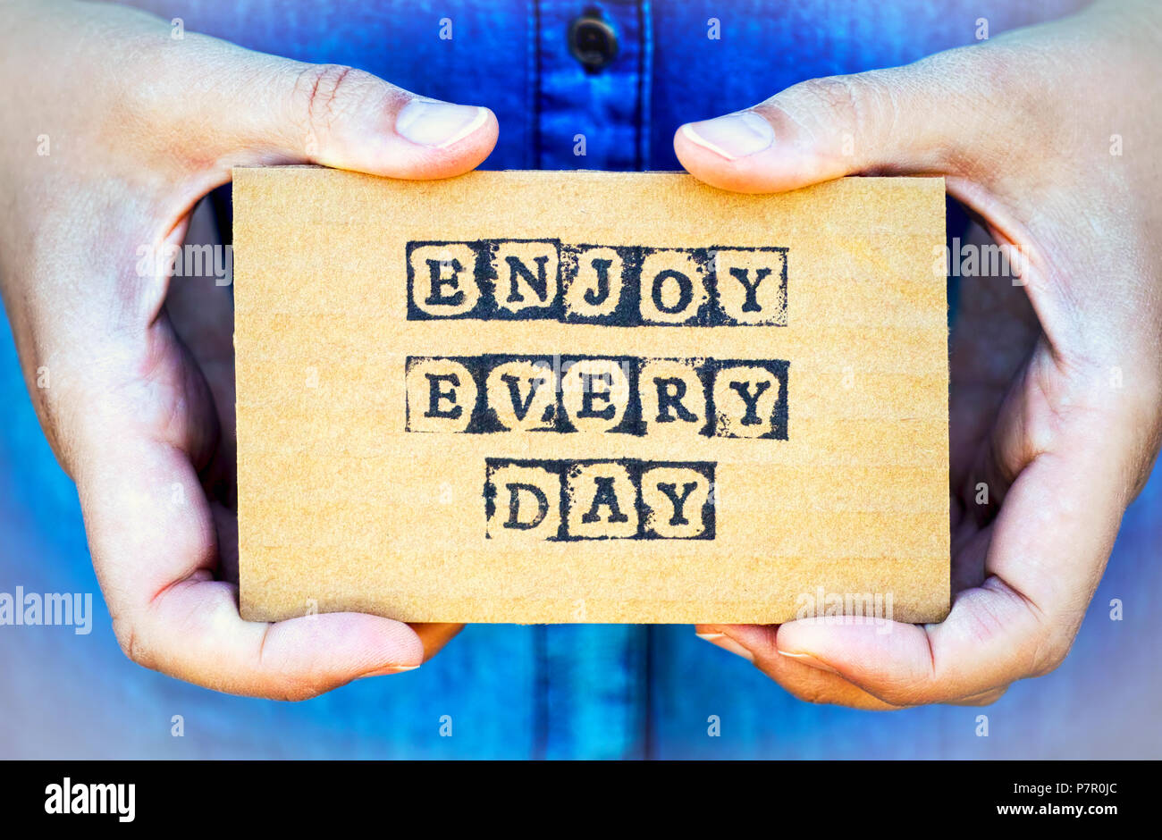 Woman hand holding cardboard card with words Enjoy Every Day made by black alphabet stamps. Denim backgrounds. - Stock Image