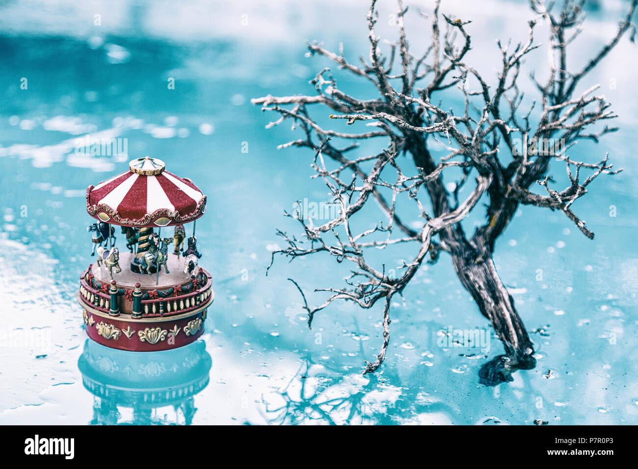 Tree and carousel on an frozen lake - Stock Image