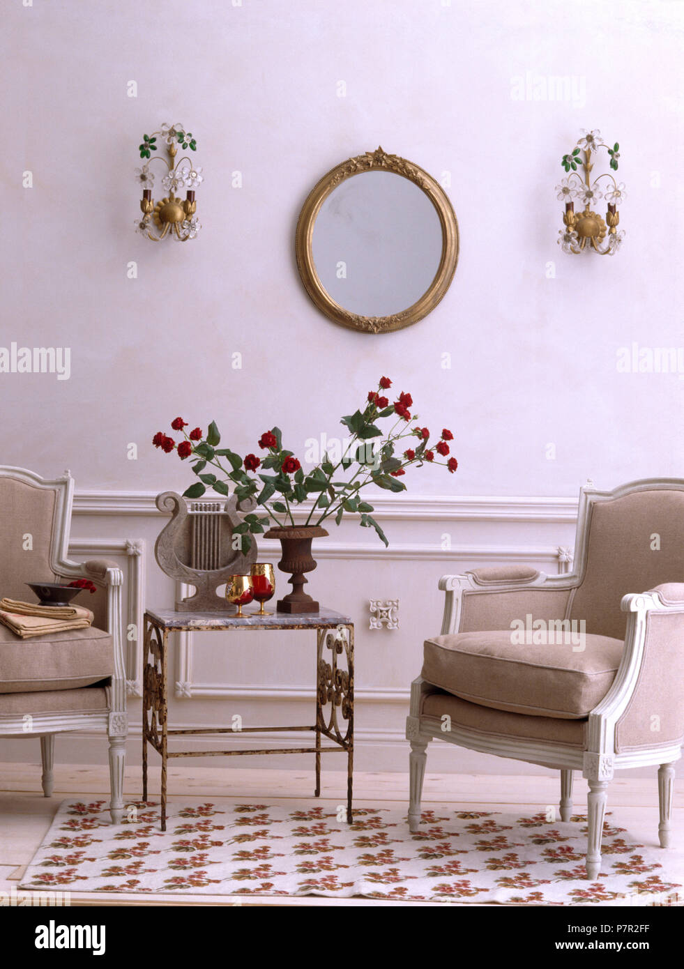 Grey upholstered painted French style chairs and small metal table in an economy style living room with wall lights either side of mirror Stock Photo