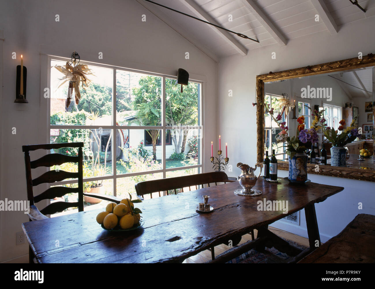 Assorted Wooden Chairs And Rustic Wooden Table In White Californian Dining Room With Mirror And Large Window Stock Photo Alamy