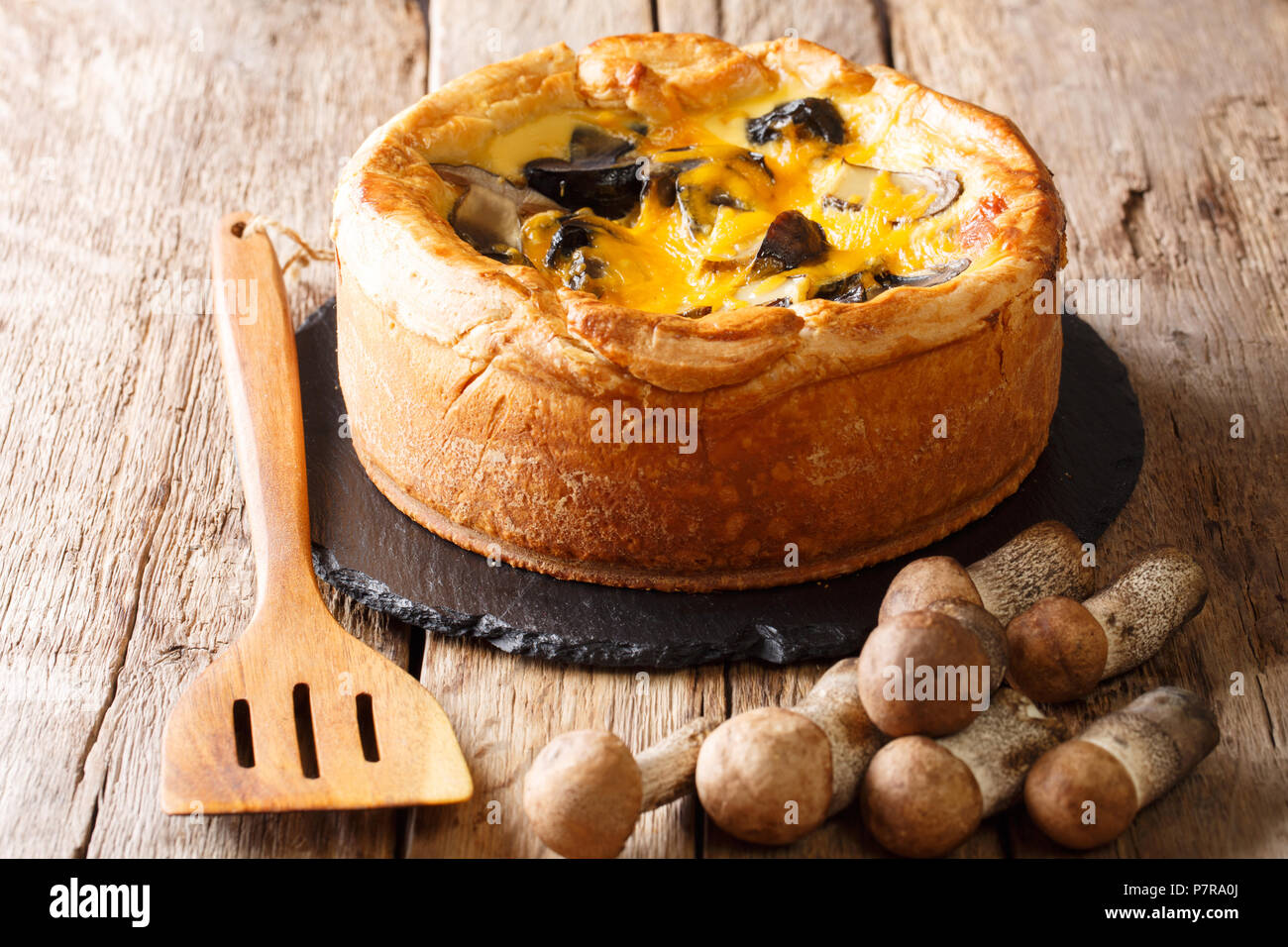 Delicious savory pie with wild mushrooms, cheddar cheese, chicken and cream close-up on the table. horizontal - Stock Image