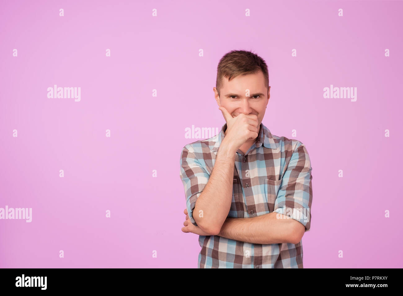 Shot of attractive young caucasian man looking at camera with cunning funny expression, closing his mouth - Stock Image