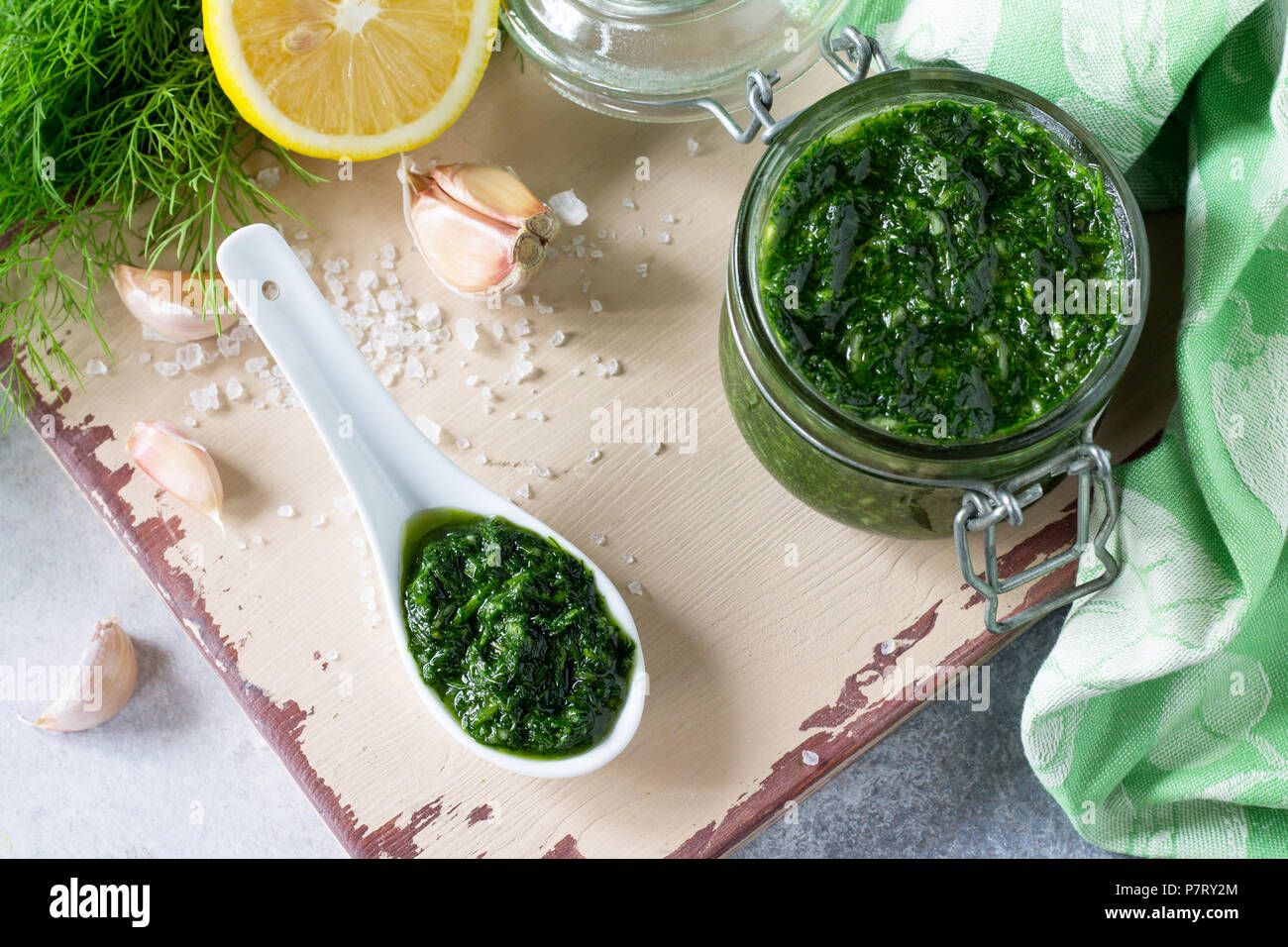 Preserving sauce dill with garlic and olive oil on the kitchen wooden background. - Stock Image