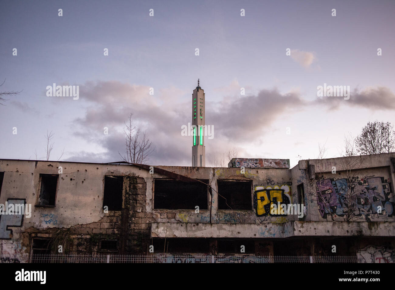 Minaret of the mosque behind the building damaged by artillery shelling of the Bosnian Civil War, Sarajevo, Bosnia and Herzegovina Stock Photo