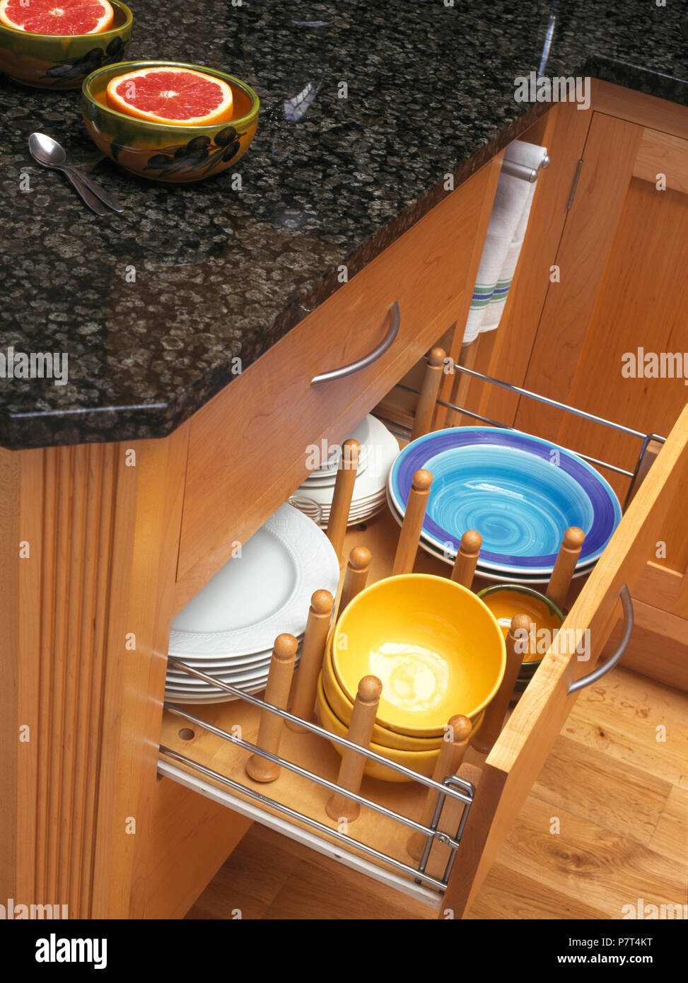 Kitchen unit with open drawer storing plates and bowls - Stock Image