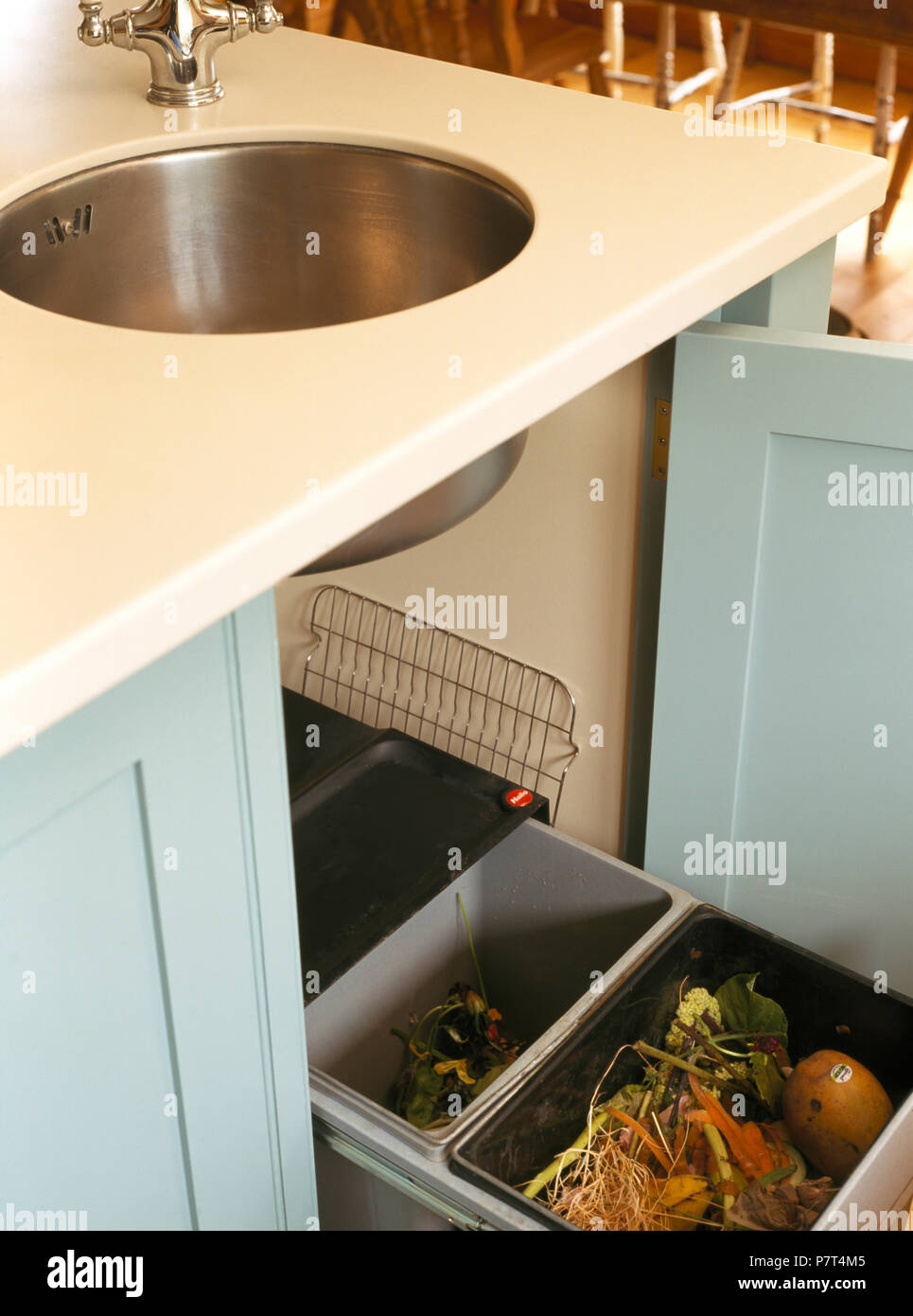 Circular stainless steel sink in kitchen unit with door open to show compost bins Stock Photo