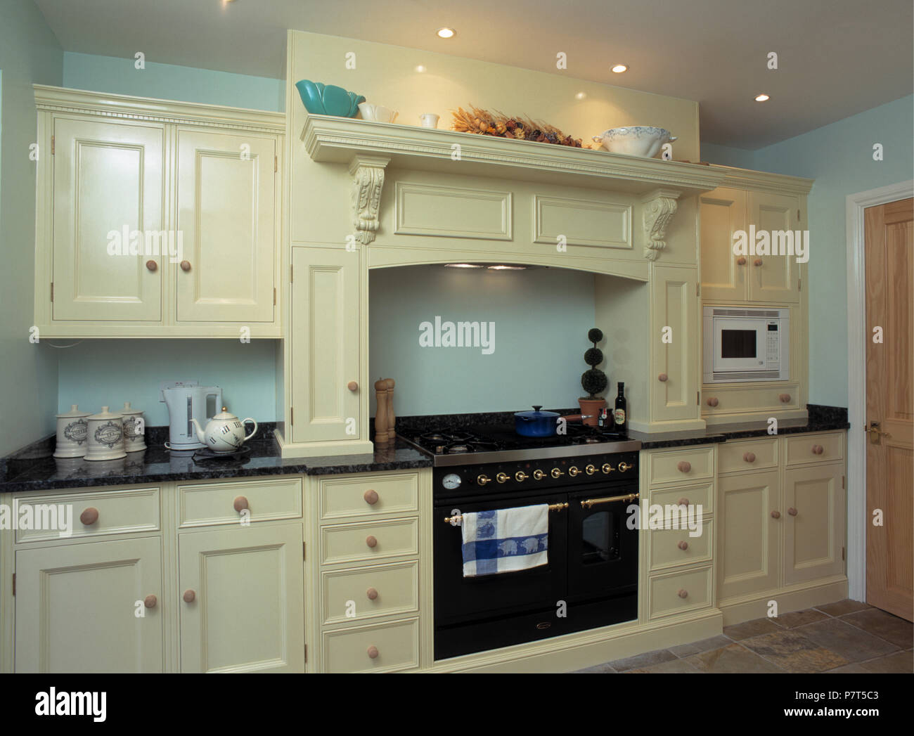 Contemporary Pastel Turquoise Kitchen With Range Oven And Cream Fitted  Cupboards With Black Granite Worktops