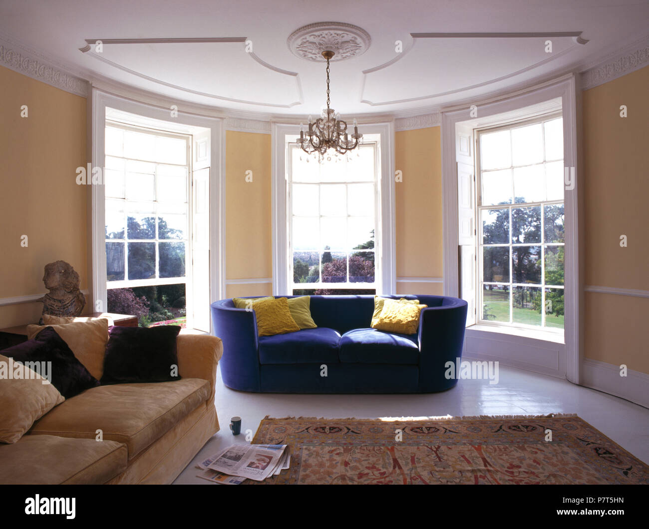 Blue sofa in bay window of large country sitting room Stock Photo