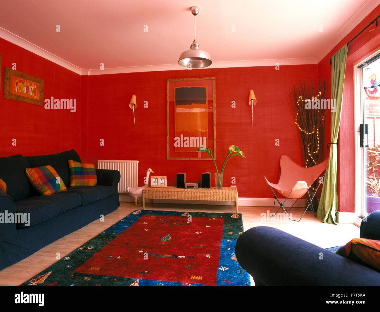 Red Blue Rug And Blue Sofa In Bright Red Nineties Living Room Stock
