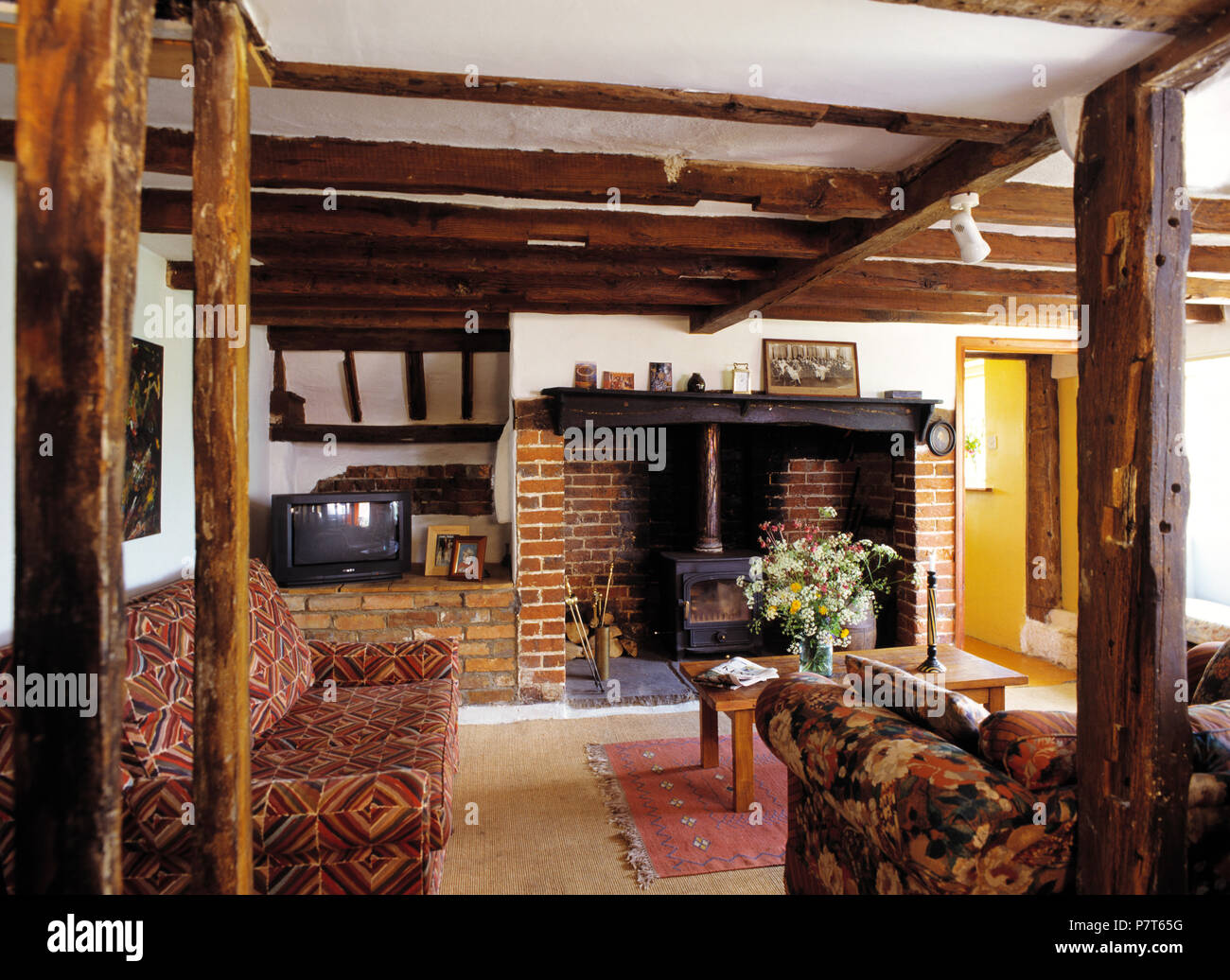 Patterned sofas and rustic wooden beams in eighties style country ...