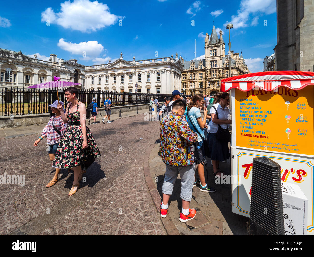 Tourists walk and buy Ice Cream on a sunny day in Central Cambridge,  between Kings Parade and Trinity Street, University buildings in the background - Stock Image