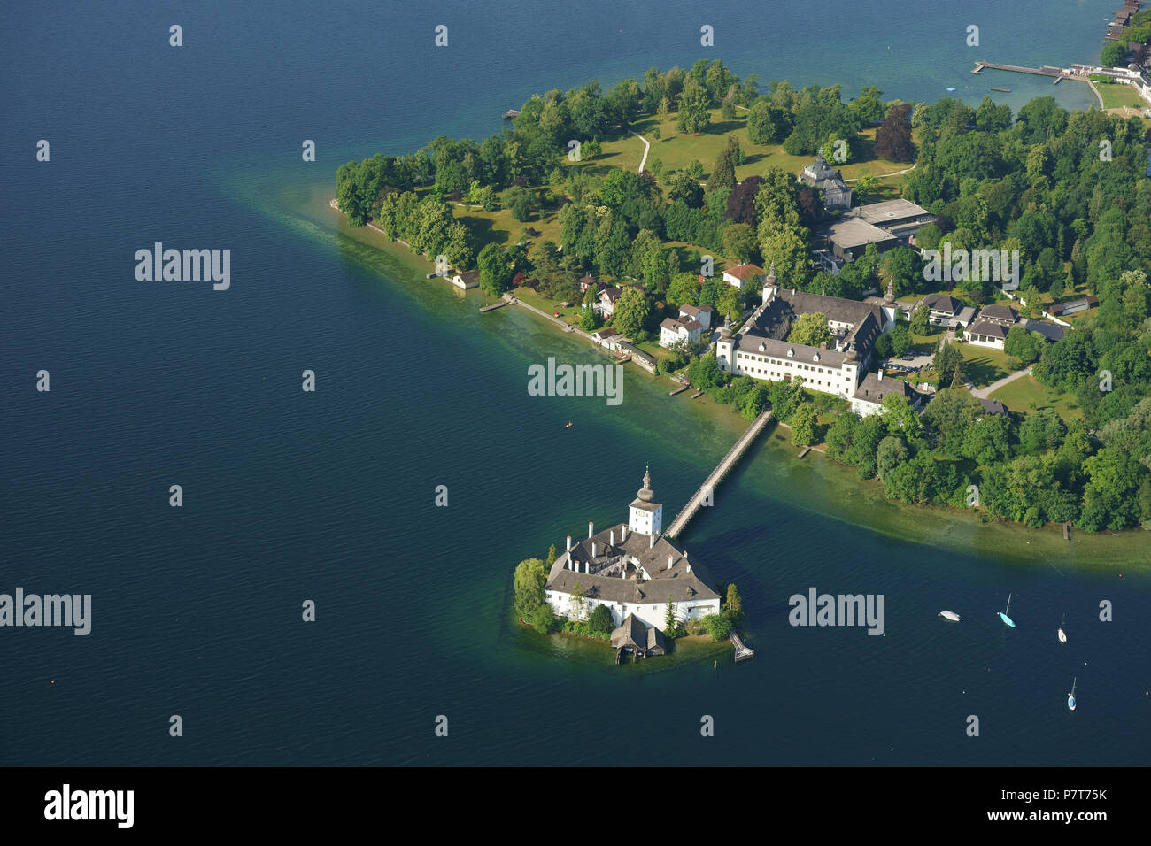 MEDIEVAL CASTLE ON A LAKE WITH A FOOTBRIDGE FOR ACCESS (aerial view). Ort Castle, Gmunden, Traunsee (lake), Upper Austria, Austria. - Stock Image