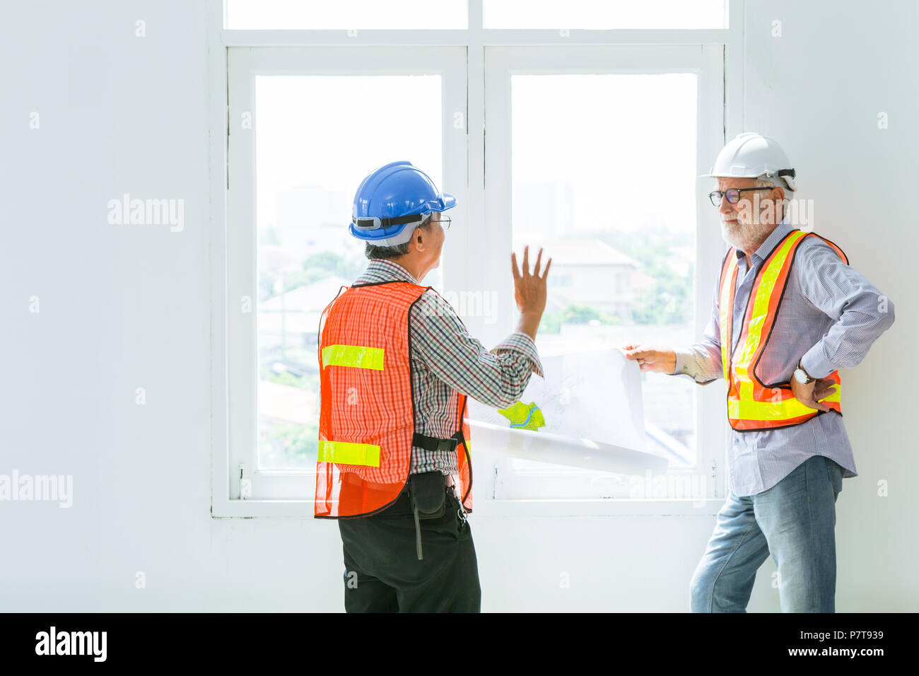 98b136a46bd6c mix race senior construction engineers worker talking together about future  of design with blueprint