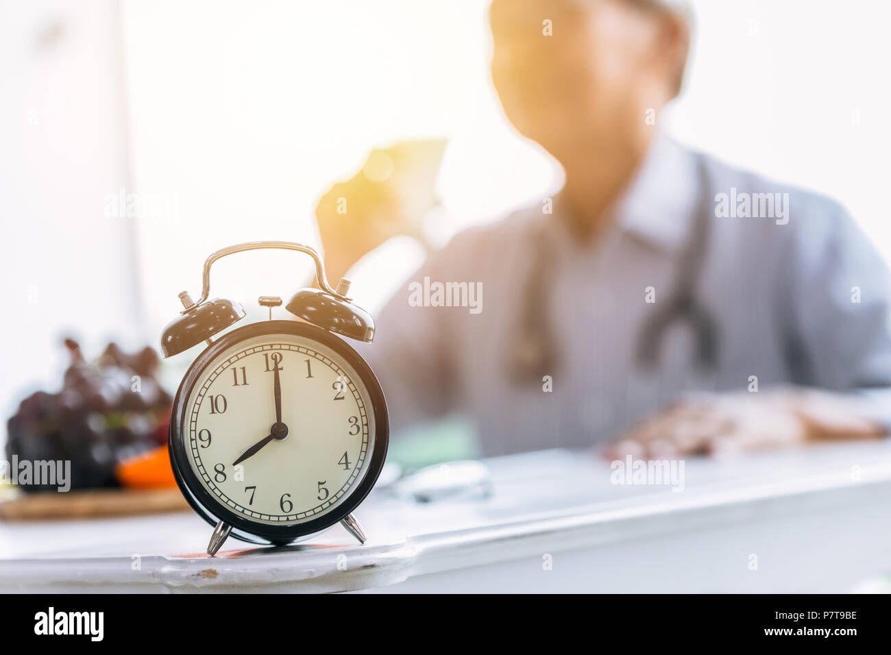 Clock on doctor clinic table for times to healthcare checkup time appointment concept. Stock Photo