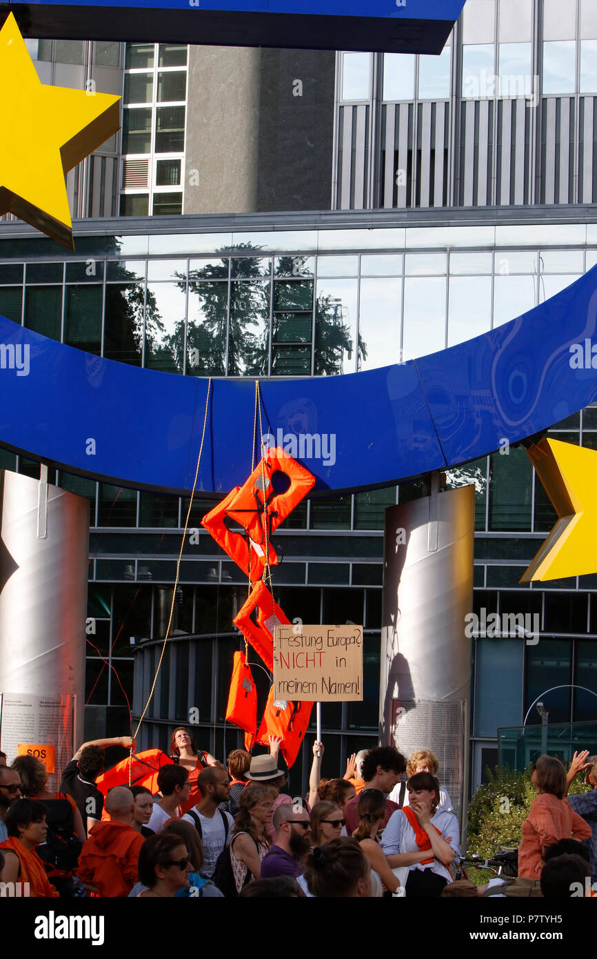 Frankfurt, Germany. 7th July 2018. Several life jackets hang from the large Euro sign outside the former seat of the ECB. Around 800 protesters marched through Frankfurt to protest against the politics of the German government and the EU of closed borders and the prevention of sea rescue operations of NGOs, by grounding their ships in Malta, that causes refugees to drown in the Mediterranean. They called for the Mayor of Frankfurt to declare Frankfurt a safe haven city for refugees from the Mediterranean. The protest was part of the German wide Seebrucke (Sea bridge) protest that saw thousands Stock Photo