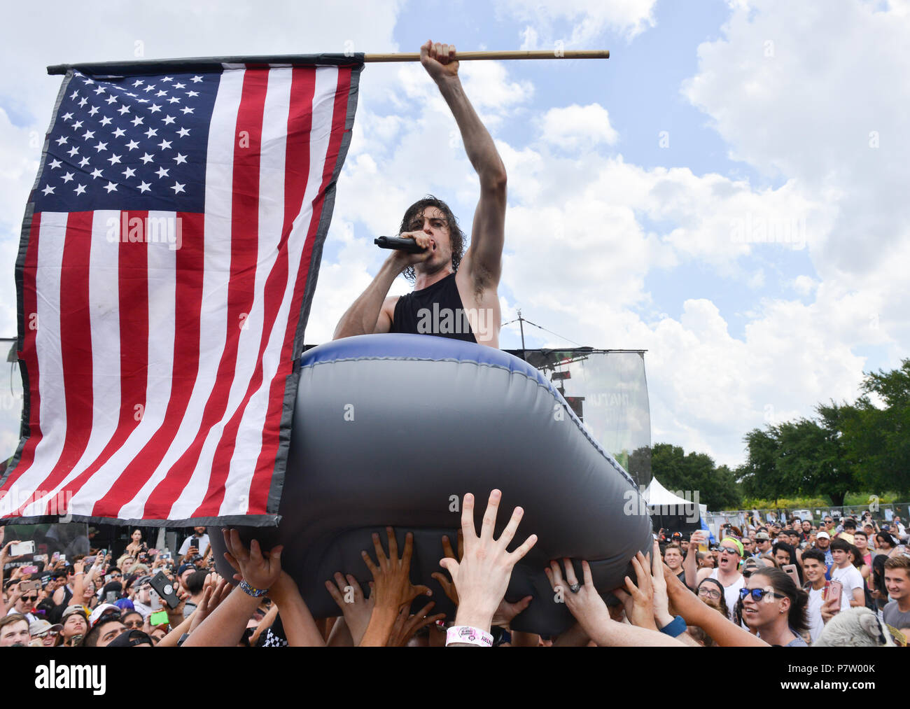Jake Taylor of In Hears Wake sings while waving the American flag and being carried over the crowd in an inflatable boat during the Van's Warped Tour at the AT&T Center Saturday. Credit: Robin Jerstad/Alamy Live News - Stock Image