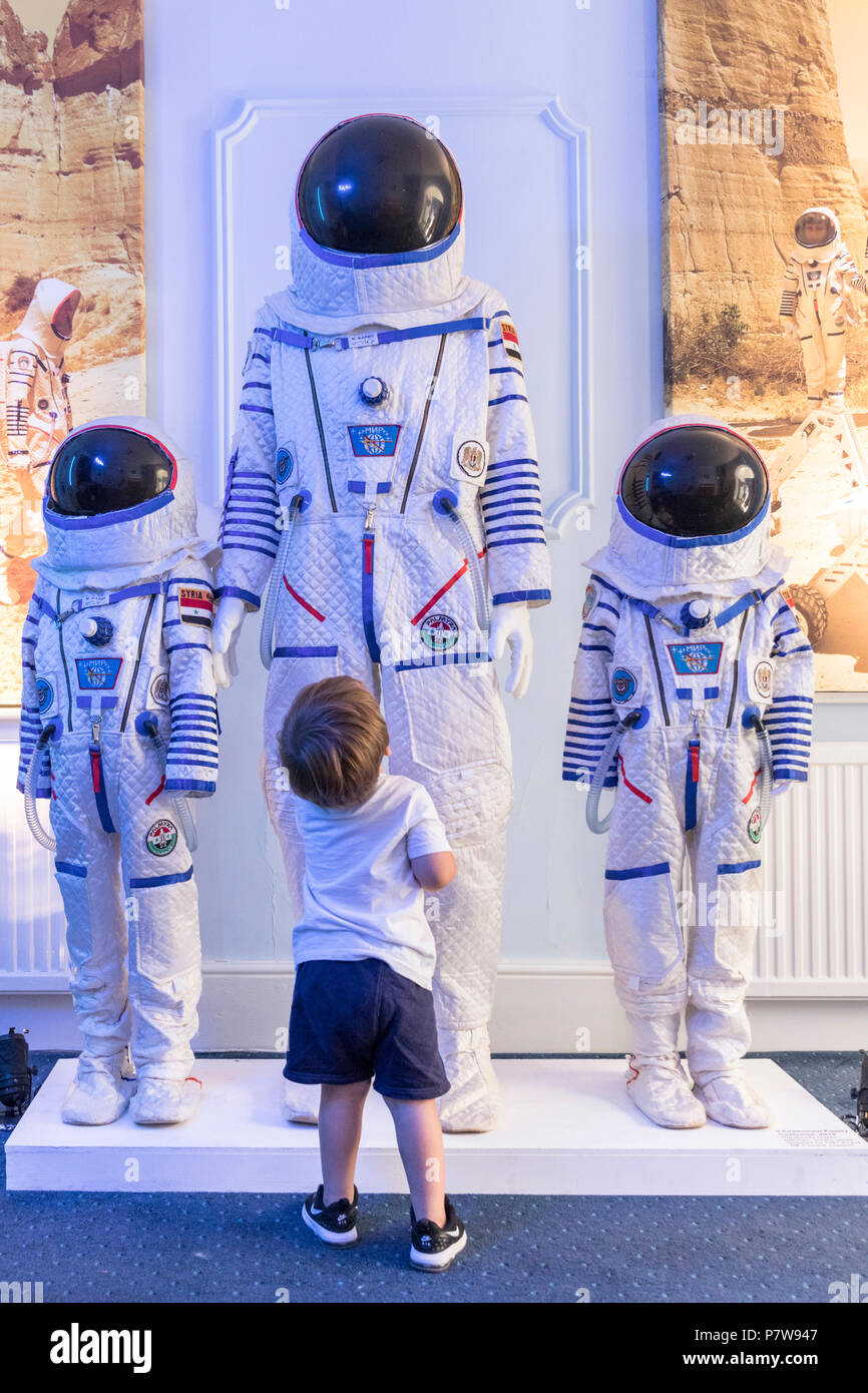 London, 8th July 2018.TA young boy, here with his dad, enthusiastically explores the space suits. The British Interplanetary Society features the 'Space Refugee' installation, about first Syrian cosmonaut Muhammed Faris. Art Night 2018 features 12 special projects curated by Hayward Gallery and over 50 presented in Art Night Open curated by cultural organisations and creatives throughout South Bank, Vauxhall and Nine Elms, on Saturday 7th and Sunday 8th July. Credit: Imageplotter News and Sports/Alamy Live News - Stock Image