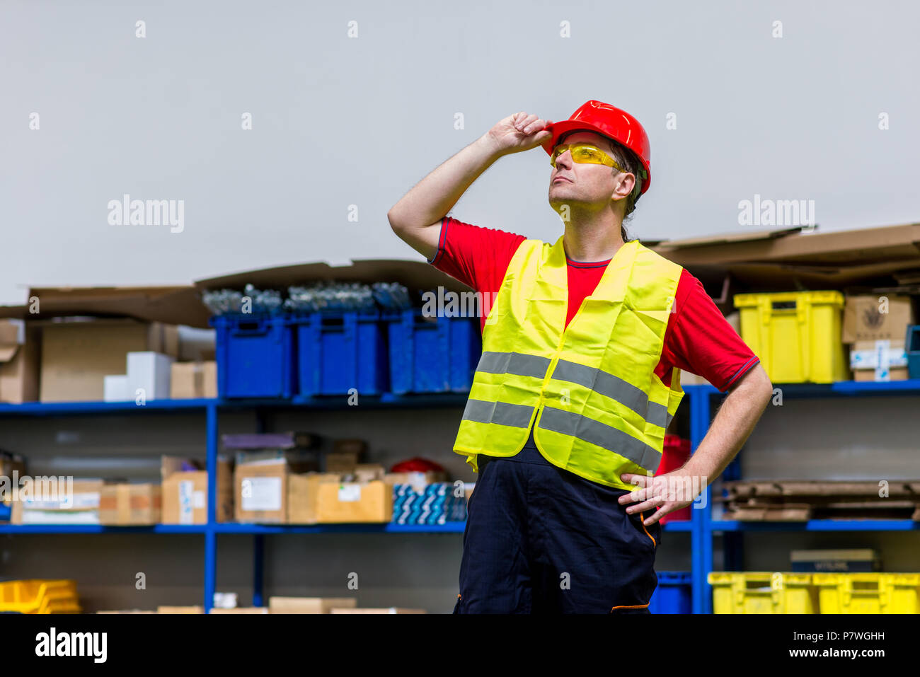 Factory worker wearing yellow reflective west, yellow safety glasses and red helmet. Factory worker looking up with one hand on his helmet - Stock Image