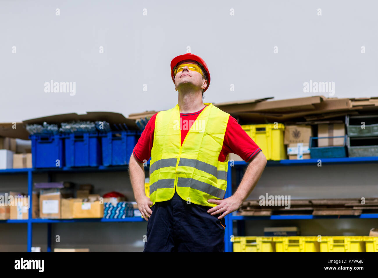 Factory worker wearing yellow reflective west, yellow safety glasses and red helmet. Factory worker with hands on his hips looking up - Stock Image